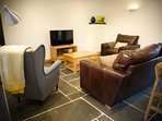 Plenty of comfy seating surrounds the flat screen TV and wood burner