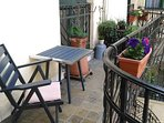 the interior 9 m2 sunny terrace with flowers , balcony table and armchair great for morning coffee