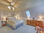 This open and airy bedroom boasts a plush queen bed.