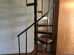 Spiral stairs going up to kitchen/bath and living area with additional sleeping.