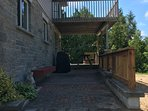 Back stone patio with gas BBQ and picnic table