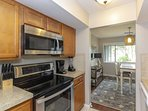 Kitchen with stainless appliances opens to dining and living area.