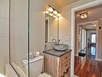 Full bath with elegant glass and tile shower, off the main hall.