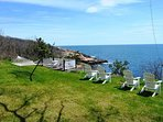Adirondack chairs on the lawn, overlooking the sea.