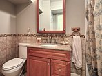 A mirrored vanity and walk-in shower fill the third bathroom.