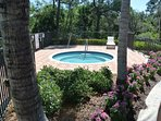 A large hot tub is located in the pool area, just steps from the condo
