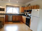 Kitchen fully equipped with large refrigerator/freezer, dishwasher, stove/oven, and microwave.
