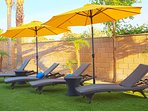 Chaise Chairs under Umbrellas with Side Tables