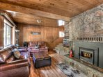 Beautiful living area with leather sofas, flatscreen smart TV,  and a wood burning stove