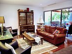 Comfortable lounge room with leather seating, TV and bluetooth sound bar