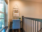 A small sitting area at the top of the stairs offers a quiet space to enjoy a good book.