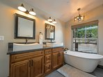A deep stand-alone tub sits in the corner of the Master Bathroom for luxuriating after a day of exploring Lake Tahoe.