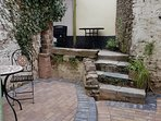 Sheltered courtyard garden with tables, chairs and kettle BBQ.  Enjoy the art on the walls!