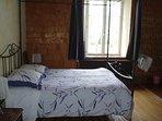 La chambre, un lit double une douche et un lavabo séparée d'un rideau. Vu sur le champ et la fôret.