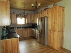 Fully equipped kitchen featuring rustic maple cabinets and granite counter tops.