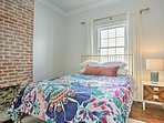 Exposed brick highlights the second bedroom.