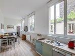 le grand séjour avec cuisine ouverte et les trois baies vitrées donnant sur le jardin des voisins