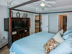 Master bedroom with sitting area, flat screen TV and ceiling fan