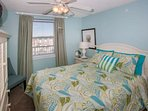 Carpeted bedroom with queen bed, sitting area and ceiling fan