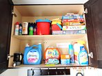 Well stocked laundry cupboard with top shelf holding games and toys / sunblock and insect  repellant