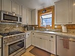 Stainless steel appliances and gleaming counters highlight the space.