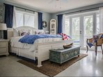Nautical inspired master bedroom with private balcony access.