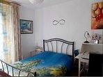 Une chambre avec un lit en 140, un balcon, un secrétaire