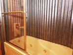 Jetted tub and shower with rustic charm in the downstairs bathroom