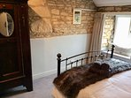 Exposed stone wall & window seat in bedroom with king-size bed