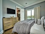 Master bedroom has flat screen TV, balcony access and attached full bathroom.