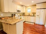 The recently renovated kitchen features new cabinets, granite counters and hardwood floors.
