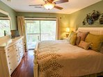 The master bedroom features a king bed, dresser, LCD TV, nightstand with reading lamp and a ceiling fan.