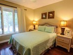 This guest bedroom features a queen bed, ceiling fan and nighstands with reading lamps.