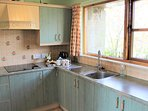 Bright well equipped kitchen with large window.