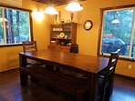 Large dining table w/ bench seats and bar stools.