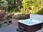 6 person hot tub with waterfall and lighting in secluded garden of silver birch trees and heathers