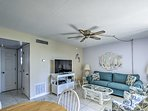 The kitchen and the living room both have ceiling fans.