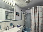 The full bathroom has a single sink, small vanity, and a shower/tub combo.