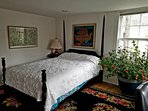 The 4-poster bed, south window and a plant that loves the light.