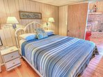 Ocean view bedroom shares the warmth of hardwood flooring and classic furnishings