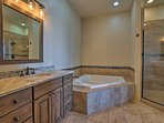 This full en-suite bathroom boasts a large walk-in shower and jetted tub.