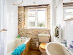 The family bathroom, in the main house, contains a bath with overhead shower, toilet and wash basin