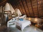 Master bedroom with traditional palapa roof.