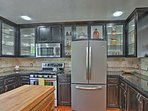 The kitchen features glass cabinet doors and stainless steel appliances.