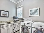 The laundry room features a brand new washer/dryer and a sink and countertop for folding clothes.