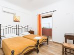 Twin bedroom on first floor with en suite bathroom, A/C, and balcony access