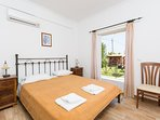 Double bedroom on ground floor with en suite bathroom, A/C, and terrace access