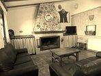 Zona de TV y chimenea de la sala de estar con techo abovedado
