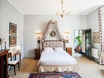 Directoire stye, evidenced by the elegant empire bed hanging over the queen size bed.