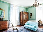 The massive 17th century armoire and huge windows grace the comfortable bedroom.